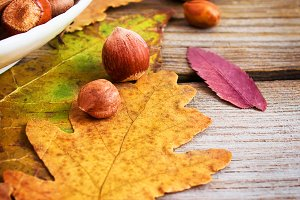 Nuts and bright autumn leaves on the wooden background