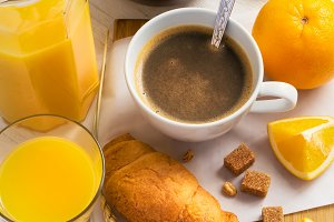 Breakfast concept - coffee, croissant and orange juice on a whit