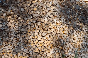 Natural wooden background with closeup of chopped firewood stacked and prepared for winter. Pile of wood logs.
