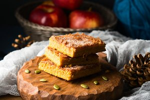 Home made pumpkin spiced square bars on wooden board