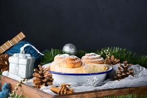 Cinnamon roll buns in enamel bowl with Christmas decorations