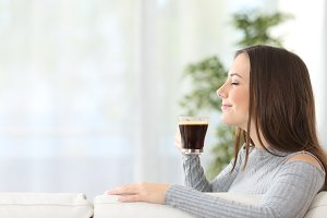 woman smelling a cup of coffee