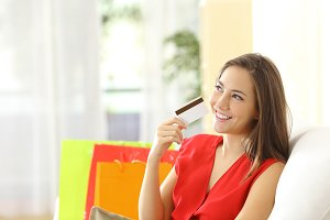 Woman thinking with credit card