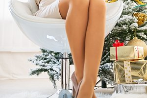 Closeup on relaxed young woman sitting near christmas tree