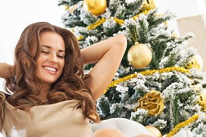 relaxed young woman sitting near christmas tree
