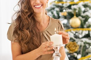 Happy young woman lighting candle near christmas tree
