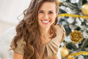 Smiling young woman among shopping bags near christmas tree