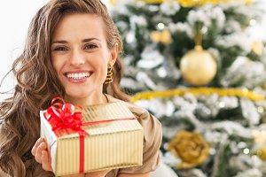 Smiling young woman with christmas present box near christmas tree