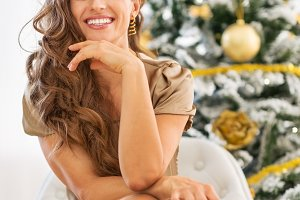 Closeup on happy young woman with shopping bags sitting near christmas tree