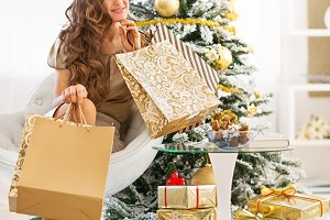 Closeup on thoughtful happy young woman with shopping bags near christmas tree