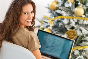 Smiling young woman using laptop near christmas tree