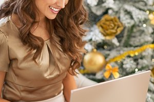 Happy young woman using laptop near christmas tree