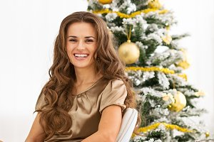Portrait of smiling young woman sitting in front of christmas tree