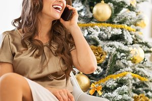 Closeup on happy young woman talking cell phone while sitting near christmas tree