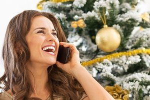 happy young woman talking cell phone while sitting near christmas tree