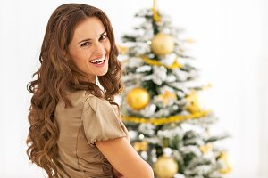 Portrait of smiling young woman near christmas tree