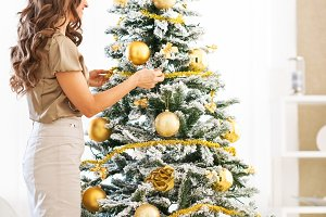 Closeup on young woman decorating christmas tree with christmas ball