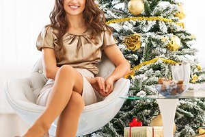 Closeup on happy young woman sitting near christmas tree