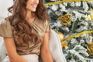 Closeup on smiling young woman near christmas tree looking on copy space
