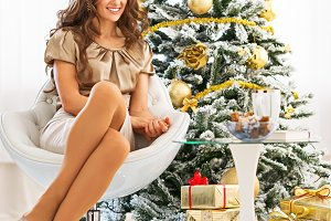 Closeup on happy young woman sitting near christmas