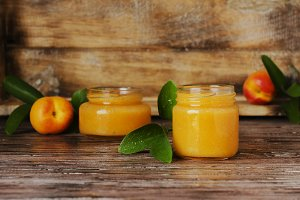 Apricot jam in small glass jars with fruits, selective focus