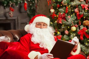 Santa Claus sitting at his home in a comfortable chair and reading letter.