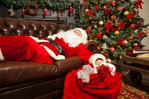 Santa Clause snoozing in a decorated living room with sack full of gifts by his side.