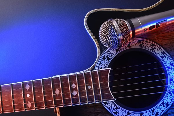Guitar and mic on table blue