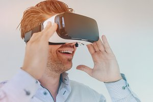 Smiling businessman using VR glasses