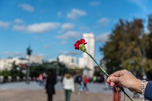 Woman holding a flower in the city