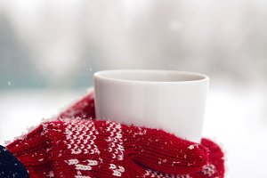 hands in red mittens holding a mug of tea
