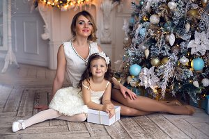 mother and daughter three years sitting at the Christmas tree