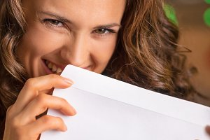 Smiling young woman hiding behind envelope