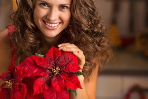 Smiling young woman with christmas rose in decorated kitchen