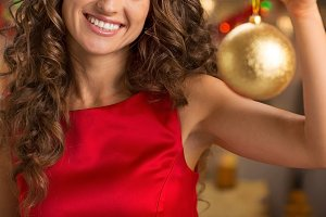 Closeup on happy young housewife showing christmas ball