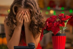 Frustrated woman waiting for a phone call in Christmas kitchen