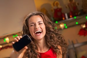 Happy young woman showing mobile phone