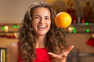 Smiling young woman throwing up orange in christmas decorated kitchen