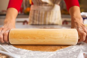 Closeup on housewife rolling out dough with rolling pin