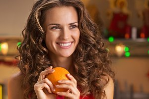Happy young housewife with oranges in christmas decorated kitchen