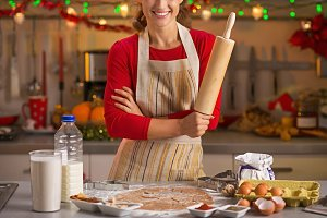 Closeup on smiling young housewife with rolling pin