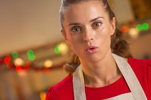 surprised young housewife in christmas decorated kitchen