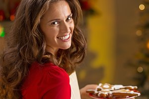 Portrait of smiling young housewife with plate of christmas cookies