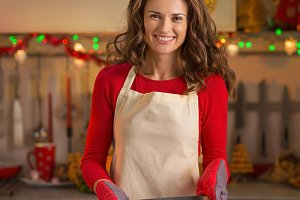 Portrait of young housewife with pan of fresh cookies in christmas decorated kitchen