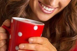 Happy young woman in christmas red dress having cup of hot beverage