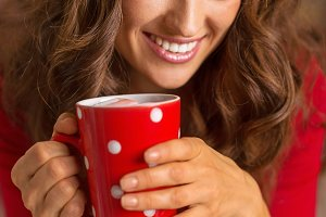 Happy young woman in christmas red dress having cup of hot bever