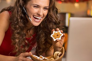 Smiling young woman showing christmas cookies while having video chat on laptop