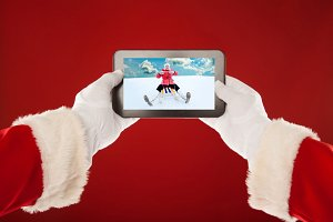 Santa Claus is holding  plate with  photo of a little girl sledding. Red background.