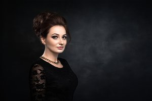 Beautiful woman on black classical dress. Vogue style photo.