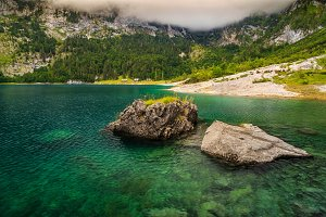 Alpine lake and foggy mountains